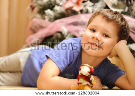Happy preschool boy portrait outside with decorated Christmas trees