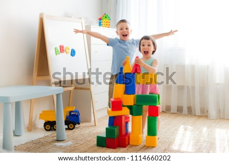 Happy preschool children play with toy blocks. Creative kindergarten children build a castle of plastic cubes. Educational toys for the family. Brothers and sisters play together in the room. stock photo