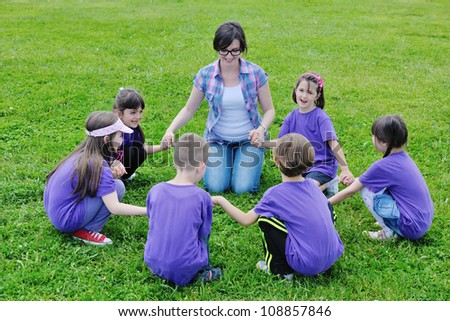 happy preschool  kids group have fun and play game  on outdoor classes in nature
