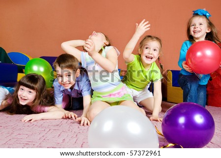 Happy preschool kids playing with balloons
