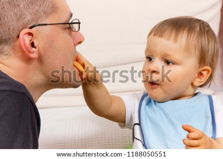 Happy preschooler eating biscuit or cookies with his father, concept of dessert for kids and parental relations #1188050551