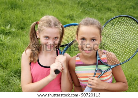 Happy preteen girls in sport outfits with tennis rackets on green