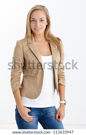 Happy pretty blonde girl in trendy jeans and jacket, smiling at camera. - stock photo