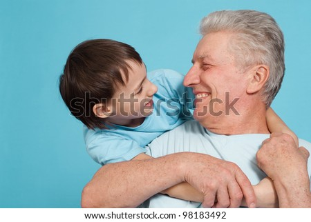 Happy pretty Caucasian grandfather with his grandson fooled on a light background