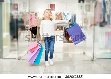 Happy pretty client, cute little girl standing in shopping centre with many colorful bags. Cheerful child doing shopping in clothing store. Kid wearing in jeans and white blouse.