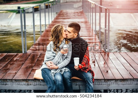 Happy pretty couple drinking hot coffee outdoor