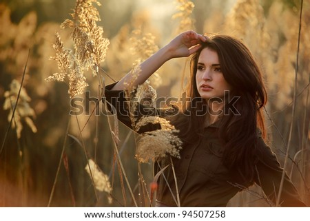 Happy pretty girl in field at sunset .Art photo #94507258