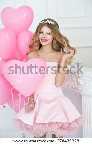 Happy pretty girl with pink balloons smiling and laughing at birthday party.