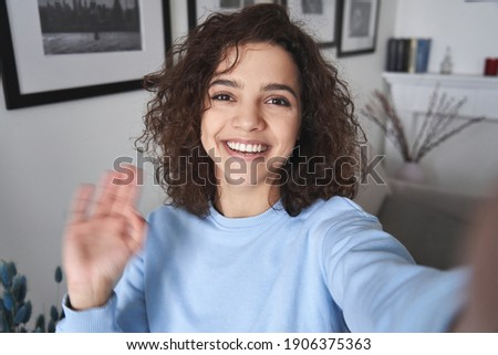 Happy pretty hispanic gen z teen girl vlogger holding smartphone waving hand, talking to camera shooting vlog, making video call at home talking by virtual mobile video call chat app. Webcam view.