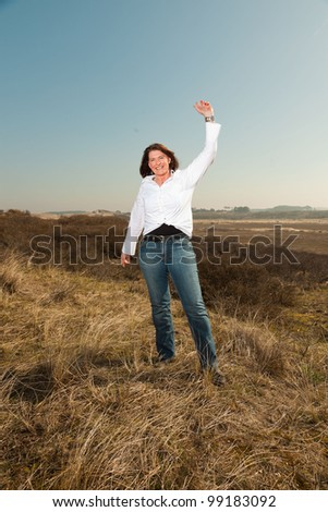 Happy pretty woman middle aged enjoying outdoors. Feeling free standing in grassy dune landscape. Clear sunny spring day with blue sky.
