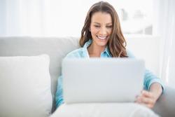 Happy pretty woman using laptop sitting on cosy sofa