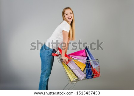 happy pretty young woman with pushcart full of colorful shopping bags isolated over grey