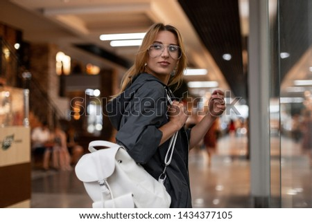 Happy pretty young woman with smile in a fashionable raincoat with hood in stylish glasses with a stylish vintage backpack is walks on a shopping center.Joyful urban girl fashion model on the vacation