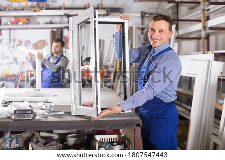Happy production workers in coverall with different PVC windows and doors Stock photo ©