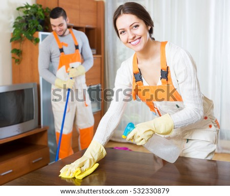 Happy professional cleaners with equipment clean furniture of client house