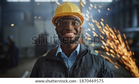 Happy Professional Heavy Industry Engineer Worker Wearing Uniform, Glasses and Hard Hat in a Steel Factory. Smiling African American Industrial Specialist Standing in a Metal Construction Manufacture. Stock foto ©