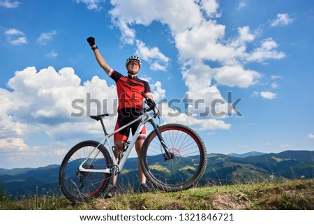 Happy professional sportsman cyclist standing with cross country bicycle on a hill, rasing hand, against blue sky with clouds on summer sunny day. Outdoor sport, success and life goals concept #1321846721