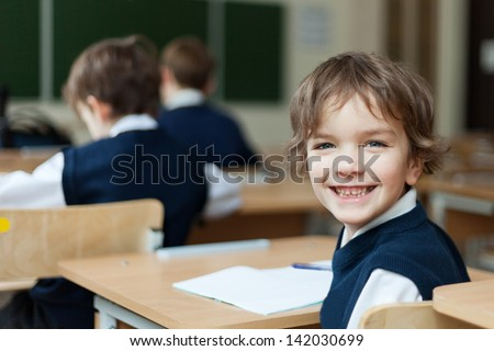 Happy Pupil in uniform sitting at  desk in school classroom