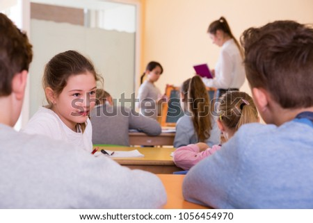 Happy pupils chattering sitting on back desks at lesson in elementary school #1056454970
