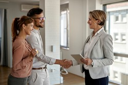 Happy real estate agent and young couple shaking hands after successful agreement.