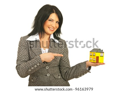 Happy real estate business woman holding and pointing to a miniature house isolated on white background
