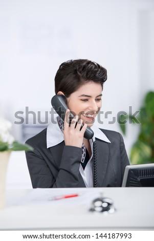 Happy receptionist conversing on landline phone at counter