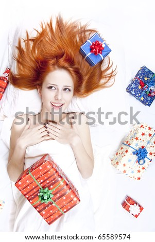 Happy red-haired girl in bed with Christmas gifts. Studio shot.