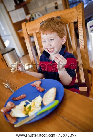 Happy redhead boy eating bacon and eggs at a table
