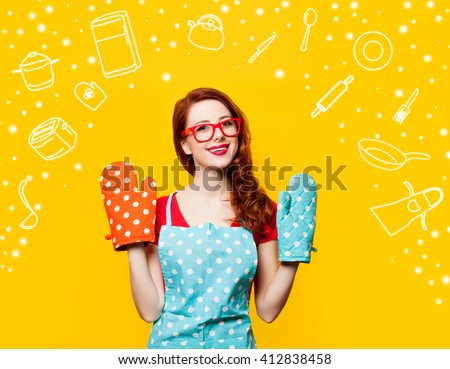 Happy redhead housewife with oven gloves on yellow background