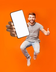 Happy redhead man jumping up in air, showing thumbs up gesture, demonstrating smartphone with empty screen, recommending new mobile application on orange studio background