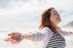Happy redhead woman relaxing with arms outstretched at beach with eyes closed. Beautiful middle aged woman felling free at sea. Smiling cheerful mid woman relaxing at the seaside with copy space.
