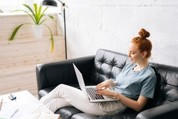 Happy redhead young woman using laptop at home sitting on soft couch. Lady is working on laptop computer. Girl student is typing message using laptop keyboard