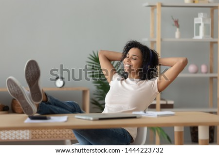 Happy relaxed african woman wear wireless headphones listening to lounge music relaxing after work hands behind head, calm serene black girl student feel stress free relief sit at home office desk