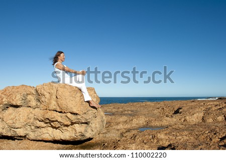 Happy relaxed confident attractive mature woman sitting on rock overlooking the ocean, isolated with blue sky as background and copy space.