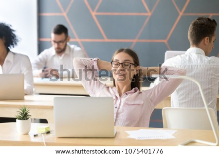 Happy relaxed female student or employee enjoying break resting from work holding hands behind head, young smiling businesswoman breathing air feeling no stress free relief in coworking office room
