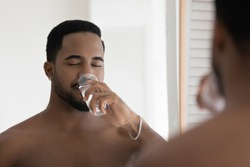 Happy relaxed handsome athletic Black guy drinking pure fresh filtered water from glass, satisfying thirst, keeping good metabolism, hydration balance, healthy morning habit. Healthcare concept