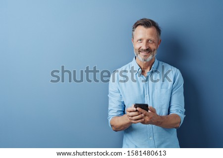 Happy relaxed man holding his mobile phone as he stands smiling at the camera over a blue studio background with copy space