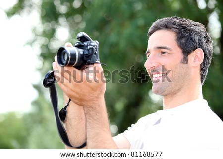 Happy relaxed man looking at the screen of his DSLR camera as he takes a photograph