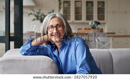 Happy relaxed mature old adult woman wearing glasses resting sitting on couch at home. Smiling middle aged grey-haired elegant senior lady relaxing on comfortable sofa looking at camera. Portrait. Сток-фото ©