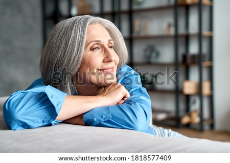 Photo of  Happy relaxed mature old woman resting dreaming sitting on couch at home. Smiling mid aged woman relaxing. Peaceful serene grey-haired lady feeling peace of mind enjoying lounge on sofa and thinking.