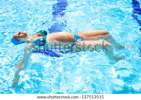 Happy relaxed pregnant woman swimming happy in beautiful swimming pool