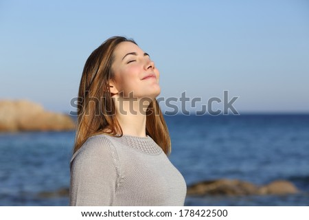 Happy relaxed woman breathing deep fresh air on the beach with the horizon in the background - Shutterstock ID 178422500