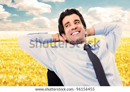 Happy relaxing businessman. Over blue sky.