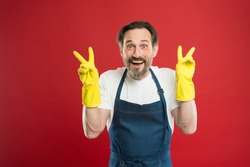 Happy relief every household day. Happy man show victory signs in rubber gloves. Household worker red background. Enjoying household routines. Cleaning and maintenance Providing household service.