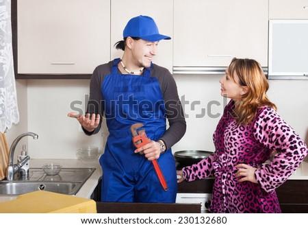 happy repairman in uniform  repairing a running water for woman in kitchen
