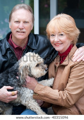 Happy retired couple embracing one another retired couple sitting with their dog