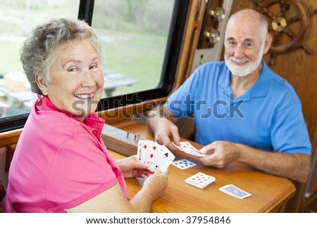 Happy retired couple playing cards in their motor home.