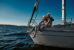Happy retired family couple relaxing on a sail boat or yacht deck floating in a calm blue sea, hugging and enjoying amazing view