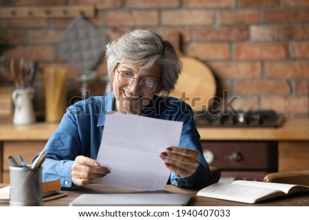 Happy retired hispanic woman bank client hold official document notification informing loan mortgage is paid. Glad smiling aged latin lady read paper letter received by mail satisfied with good news Photo stock ©