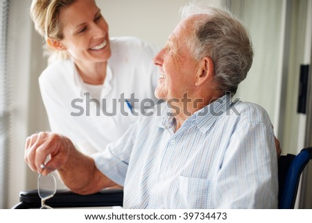 Happy retired man at the hospital speaking with a young nurse